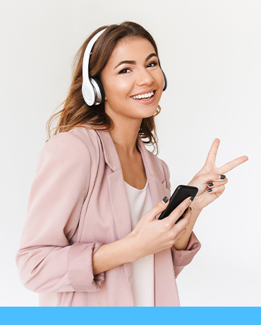 Image of young cute beautiful woman isolated over white wall background listening music with headphones using mobile phone make peace gesture.